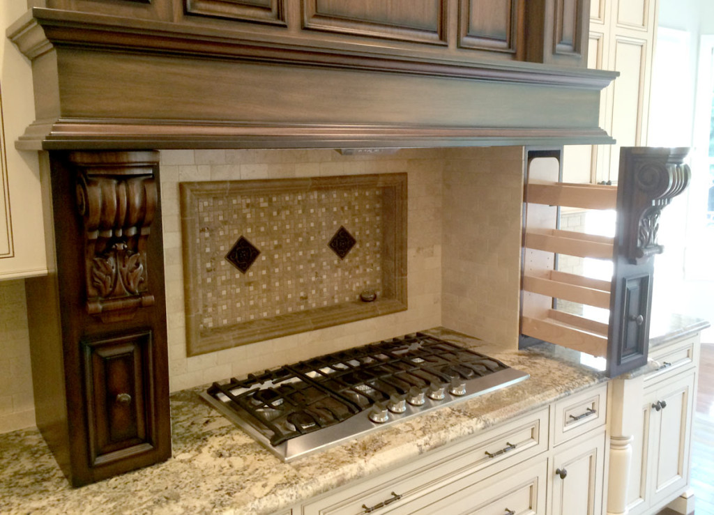 Kitchen Stovetop with Carved Wood Vent Hood and Elegant Backsplash Feature in NJ